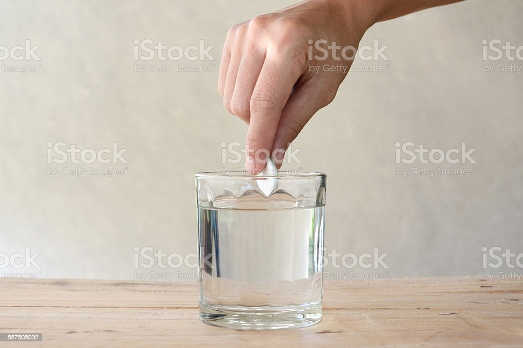 woman put effervescent tablet in glass stock photo