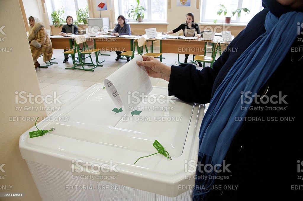 Woman put election ballot into the box stock photo