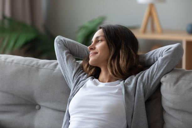 Woman put hands behind head leaned on couch resting indoors stock photo