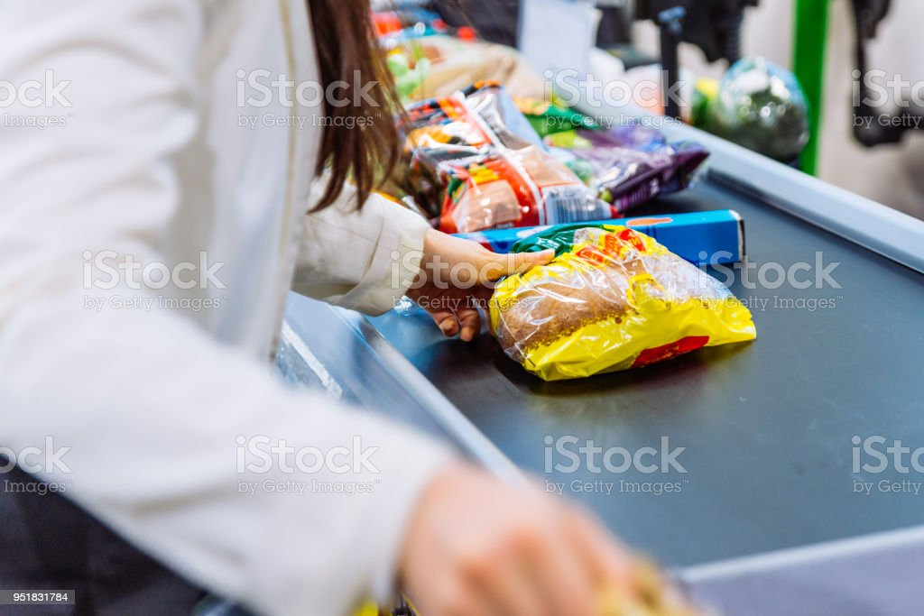 woman put products on the line near cashbox. grocery shopping concept stock photo