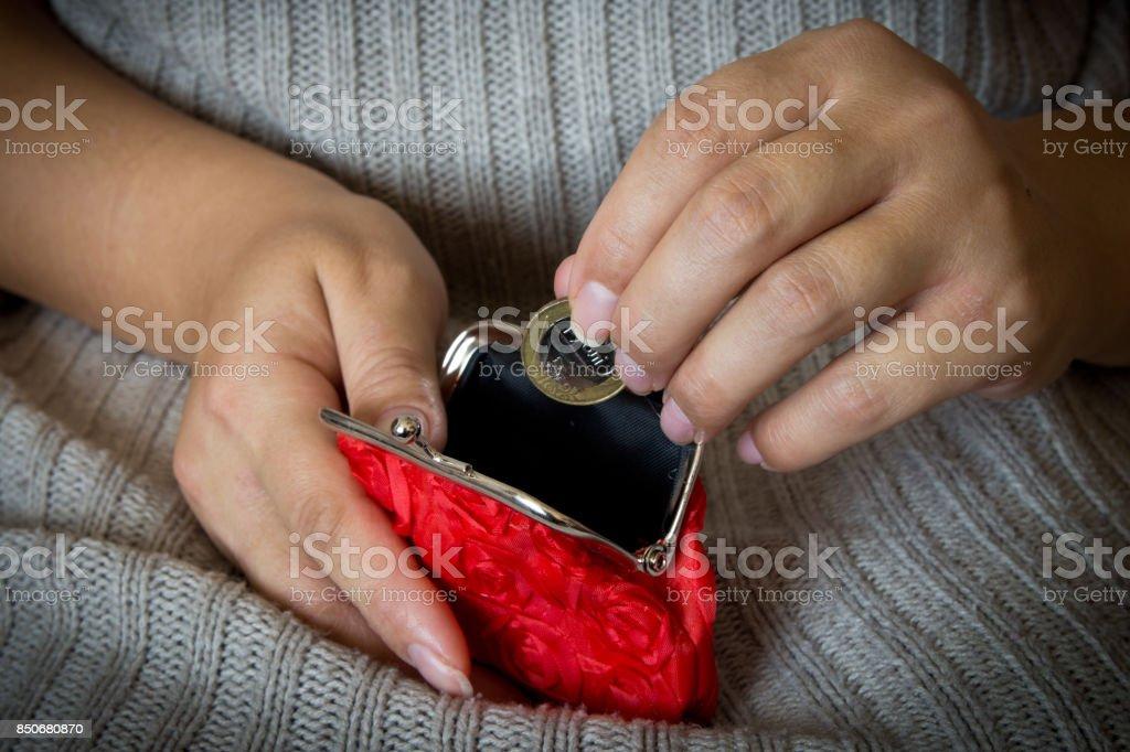 Uma mulher coloca uma moeda em uma bolsa vazia. Porta-moedas vermelhas. - foto de acervo