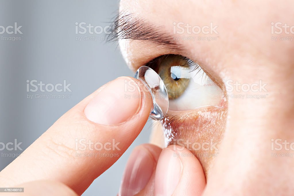Woman puts contact lens stock photo