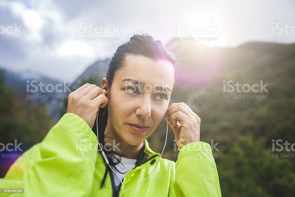Woman puts headphones on, preparation for a run stock photo