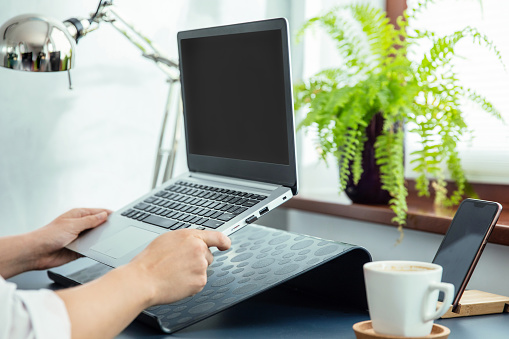 Woman puts her ultrabook to laptop's stand.
