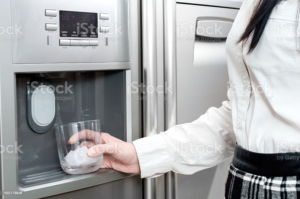 Woman puts ice cubes into the glass. stock photo