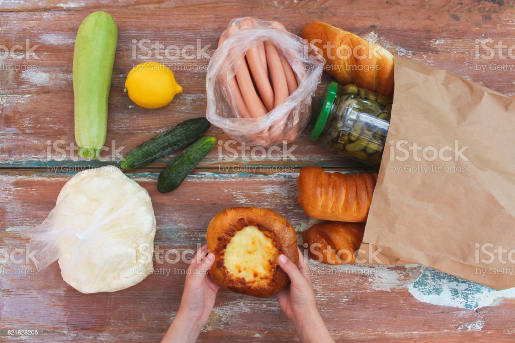 Woman puts purchase of paper bag on table. Top view. stock photo