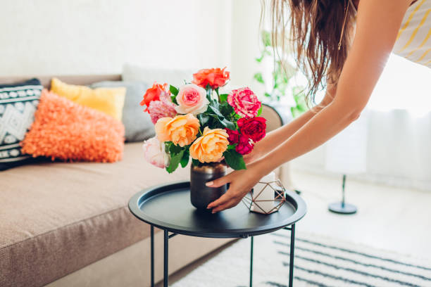 Woman puts vase with flowers roses on table. Housewife taking care of coziness in apartment. Interior and decor
