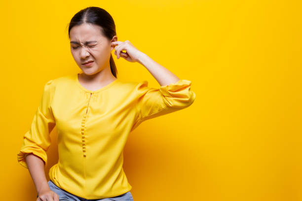 Woman putting a finger into her ear stock photo