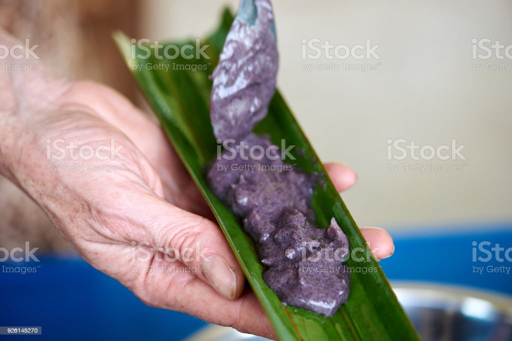 Woman putting a paste of cocount meat, suger, salt into palm lea stock photo