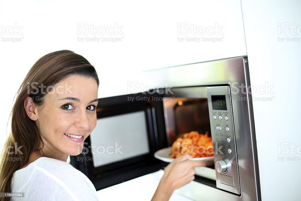 Woman putting a plate in microwave oven stock photo