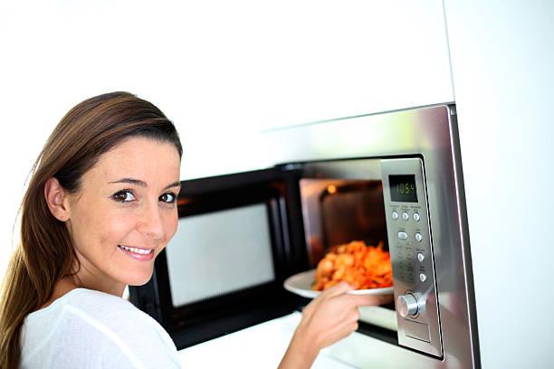 Frau putting einer Platte in Mikrowelle – Foto