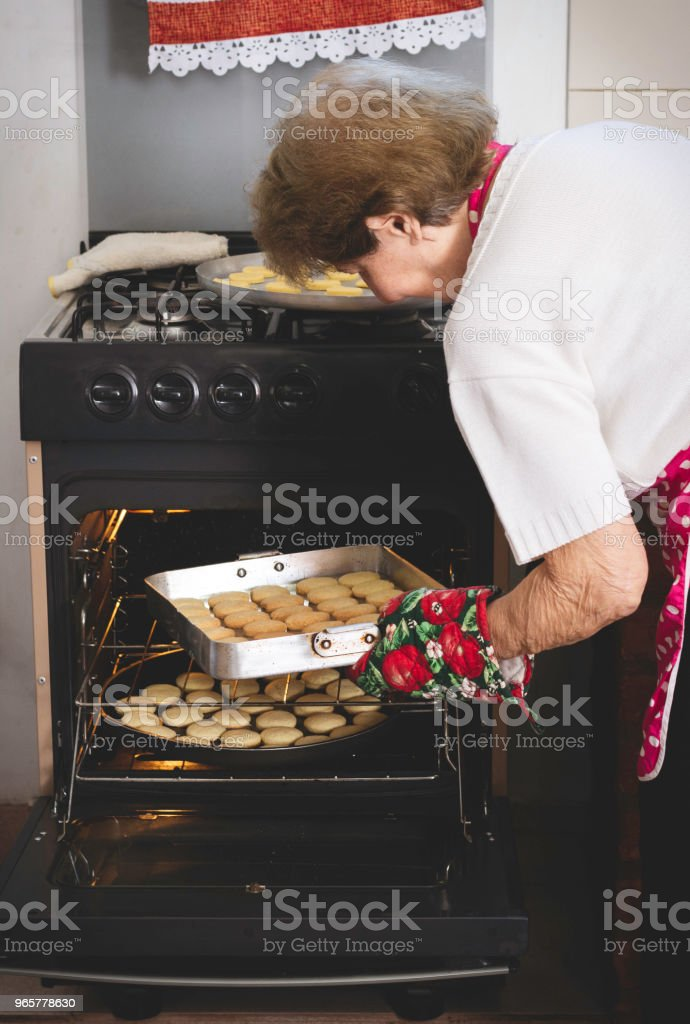Woman putting alfajores in the oven to bake. - Royalty-free 80-89 Years Stock Photo