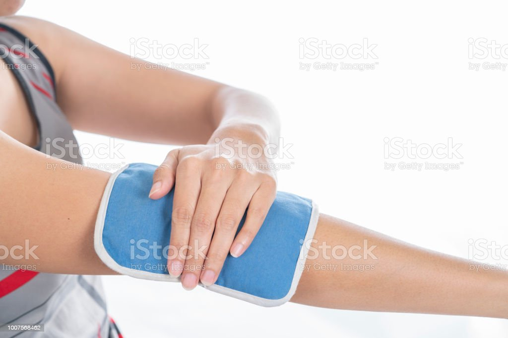 woman putting an ice pack on her arm or elbow pain, healthy concept stock photo
