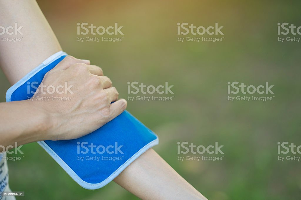 woman putting an ice pack on her arm pain stock photo