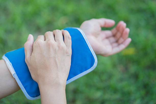donna di mettere un blocco di ghiaccio per il suo braccio dolore - crioterapia foto e immagini stock