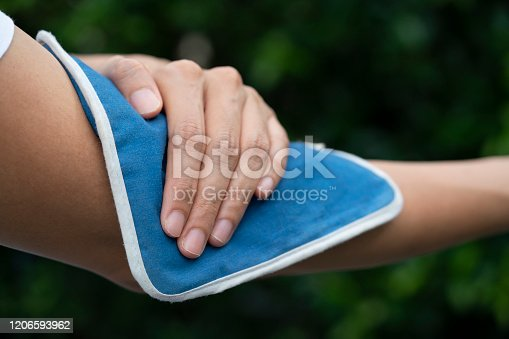 woman putting an ice pack on her elbow pain, healthy and medical concept