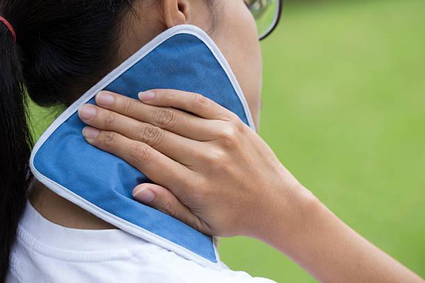 donna di mettere un blocco di ghiaccio per il suo collo dolore - crioterapia foto e immagini stock