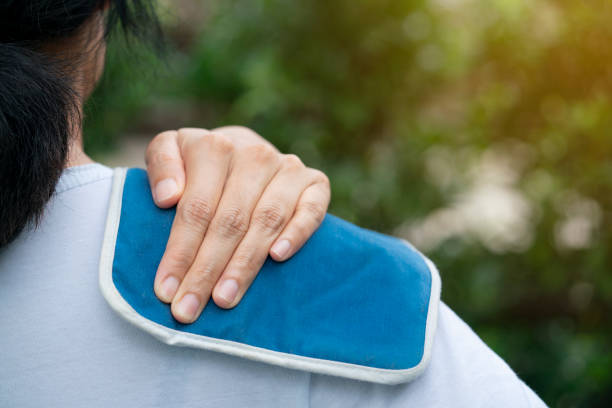 woman putting an ice pack on her shoulder pain - crioterapia foto e immagini stock