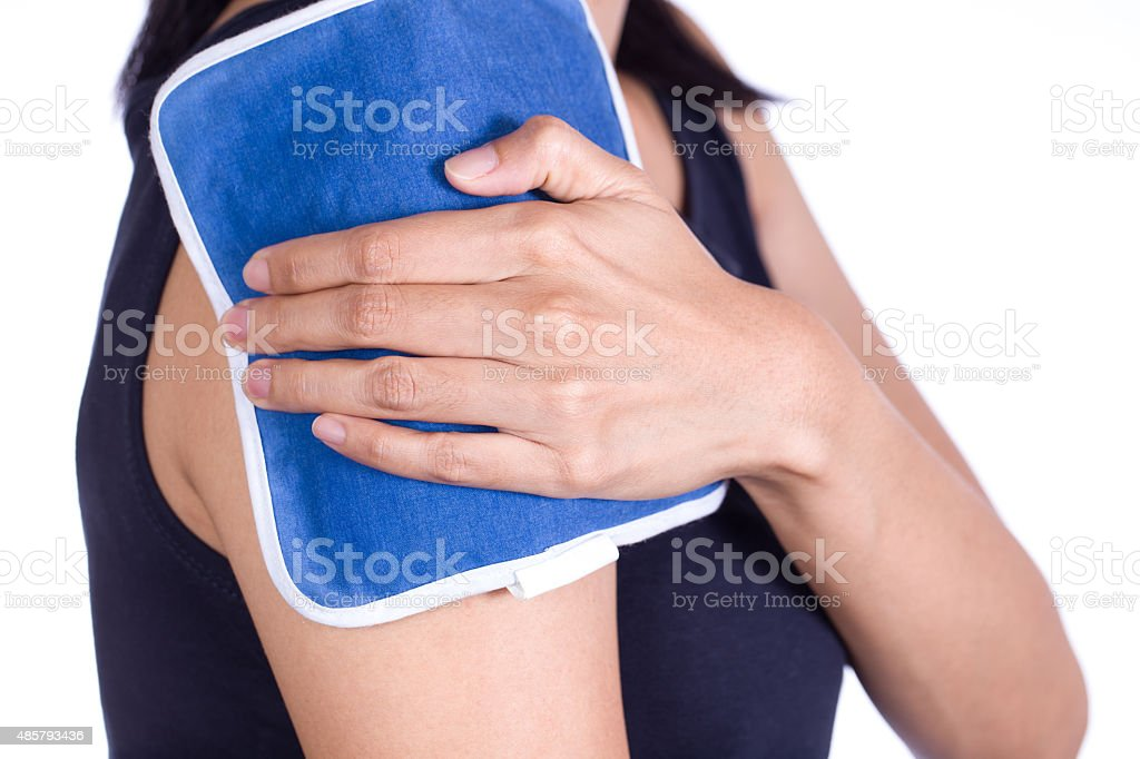 woman putting an ice pack on her shoulder pain stock photo