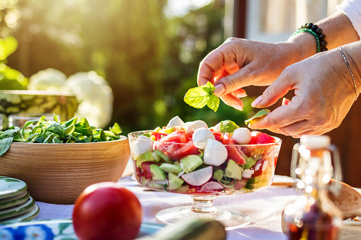 Female hand finishing fresh vegetable salad with herb basil leaves. Preparing healthy food in garden outdoors