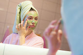Beautiful woman putting beauty mask on her face in front of the mirror at home.