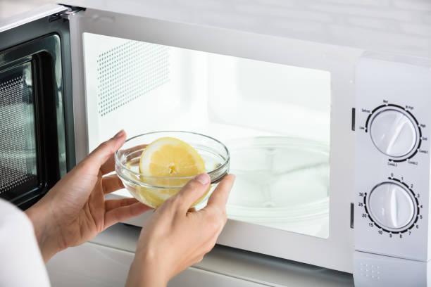 người phụ nữ đặt bát chanh lát trong lò vi sóng - clean microwave hình ảnh sẵn có, bức ảnh & hình ảnh trả phí bản quyền một lần
