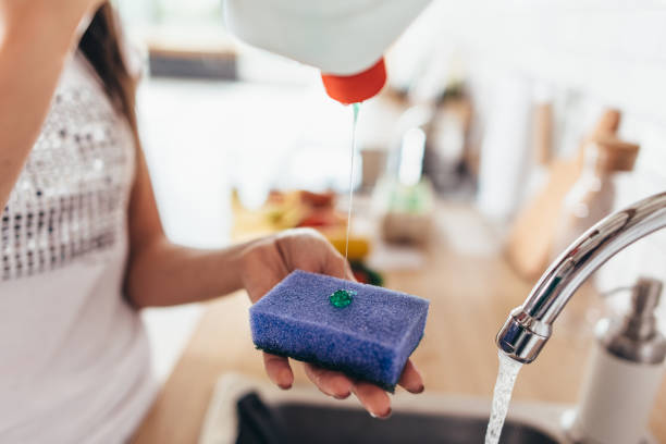 woman putting cleanser to a sponge to wash pan in the kitchen-sink. hand washing dishes. close-up. - spugna per le pulizie foto e immagini stock