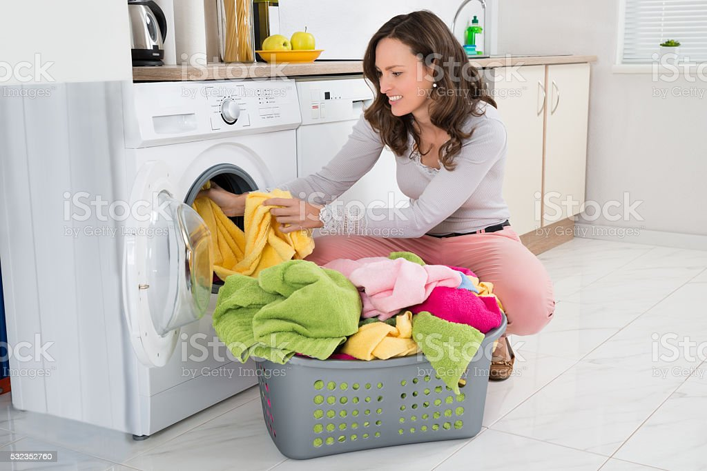 Woman Putting Clothes Into Washing Machine stock photo