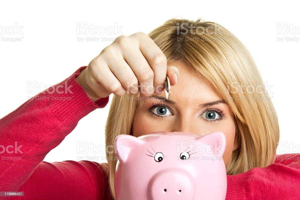 Woman putting coin in a pink piggy bank Saving Money in the Credit Crunch over white Adult Stock Photo