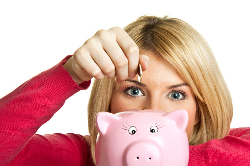Woman Putting Coin In A Pink Piggy Bank Stock Photo - Download Image Now