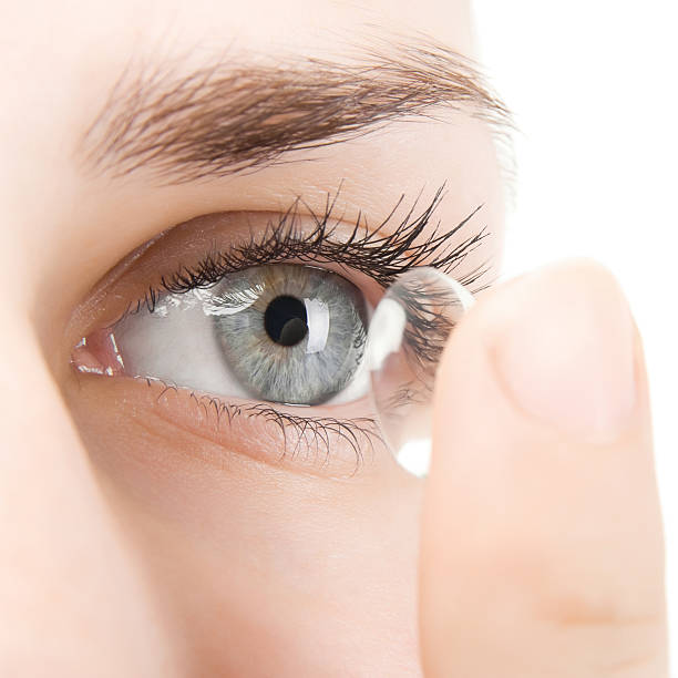 Woman putting contact lens into eye A young woman inserting a clear content lens into her left eye.  The woman's eye is blue, and she has brown eyebrows. lens eye stock pictures, royalty-free photos & images