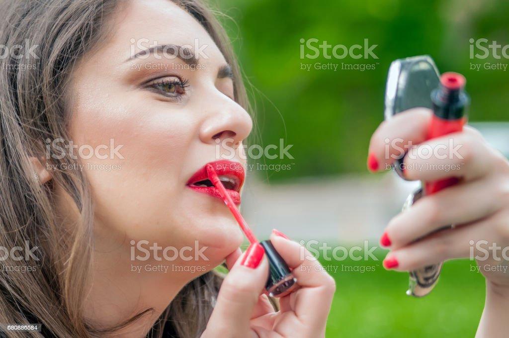 Woman putting, correcting red lipstick lip gloss. royalty-free stock photo