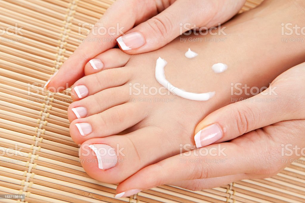 Woman putting cream in a smile shape on her foot royalty-free stock photo