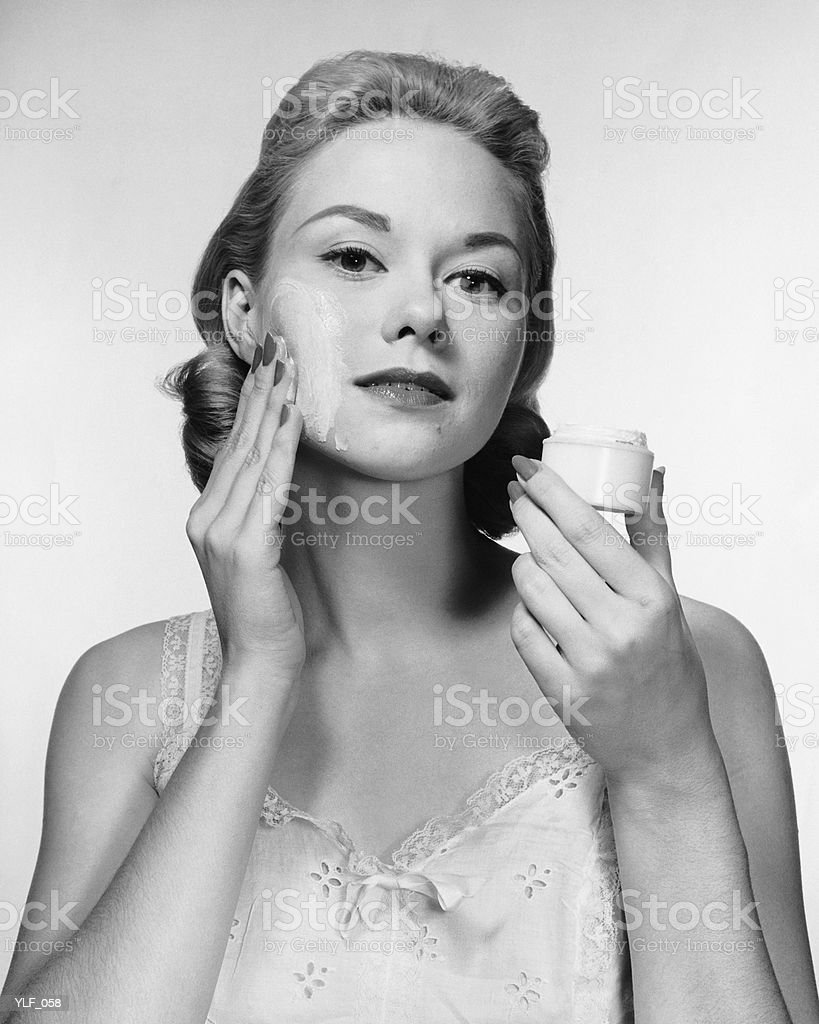 Woman putting cream on face royalty-free stock photo