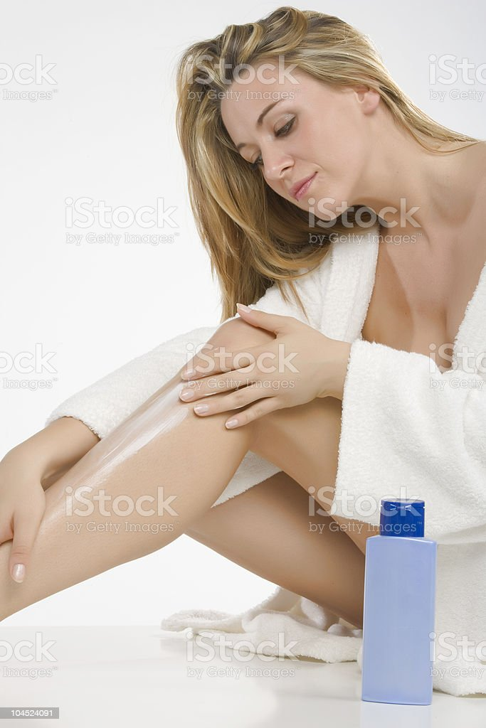 Woman putting cream on her legs royalty-free stock photo