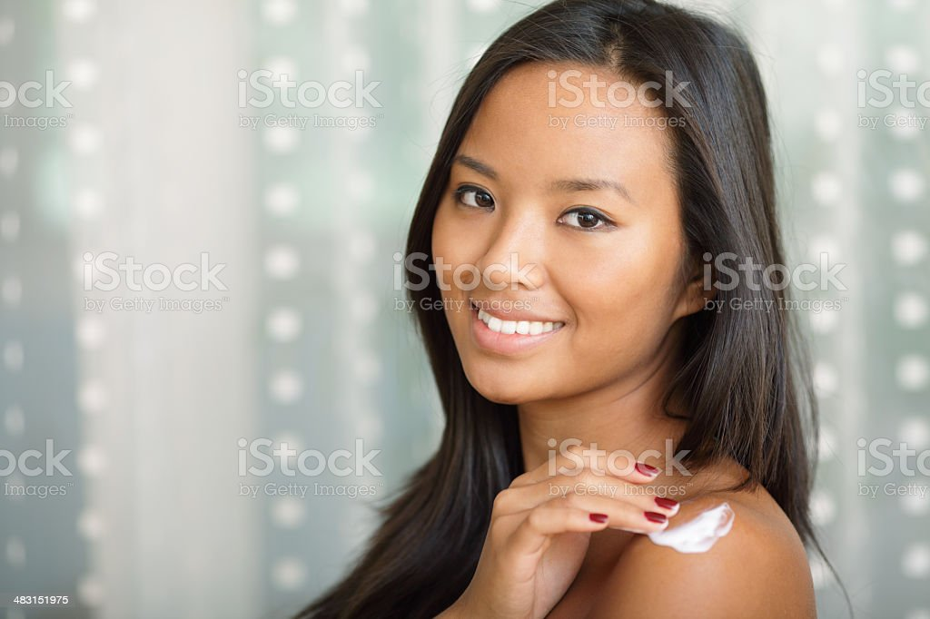 woman putting cream on her shoulder royalty-free stock photo