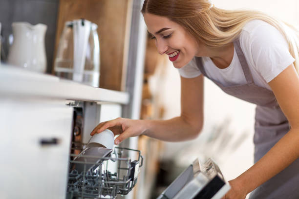 Woman putting dishes into dishwasher Woman putting dishes into dishwasher dishwasher stock pictures, royalty-free photos & images