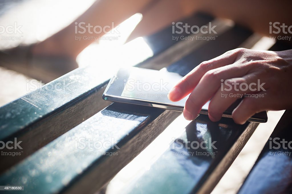 Woman Putting Down Her Phone on Bench stock photo