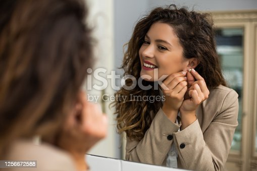 Businesswoman is  putting earrings while preparing for work.