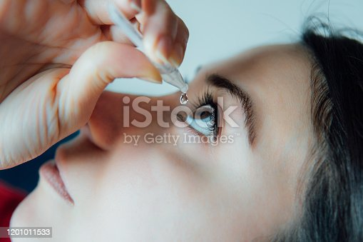 woman putting eye drops