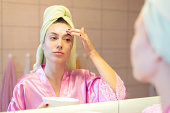 Young beautiful woman in bathrobe putting facial mask on her face in front of the bathroom mirror at home.