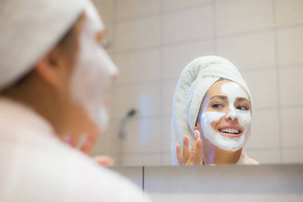 Woman putting facial mask on her face stock photo