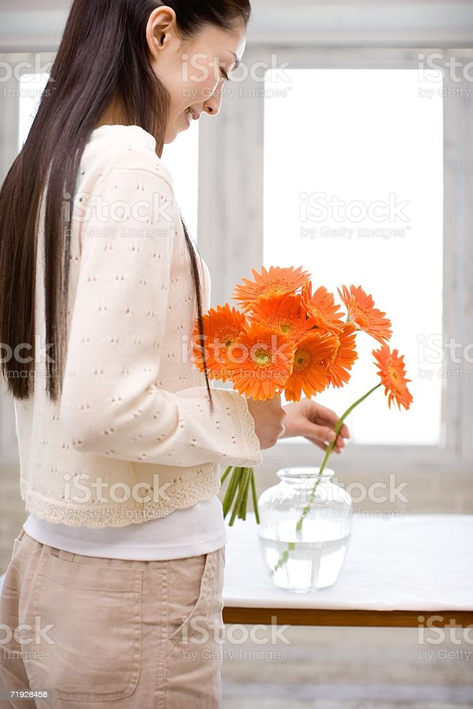Woman putting flowers in a vase royalty-free stock photo