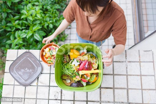 Woman putting food garbage into composter