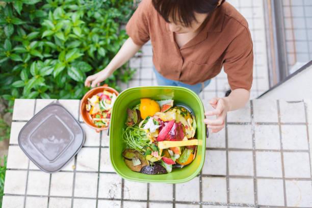 食品ゴミをコンポストに入れる女性 - sustainability ストックフォトと画像
