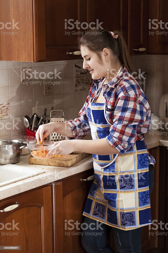 woman putting grated carrot in bowl royalty-free stock photo