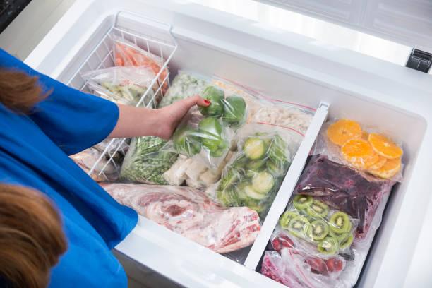 uma mulher colocando pimentões verdes na geladeira - comida congelada - fotografias e filmes do acervo