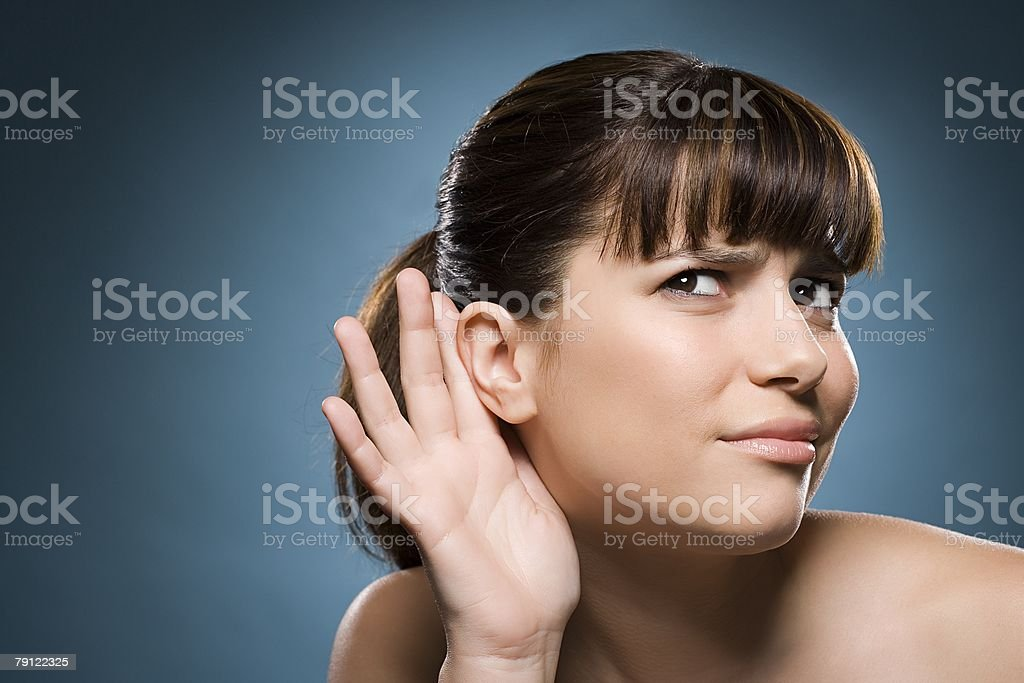Woman putting hand to her ear stock photo