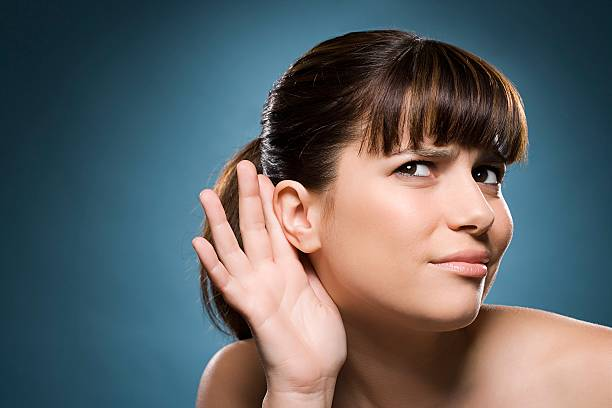woman putting hand to her ear - ear stock photos and pictures