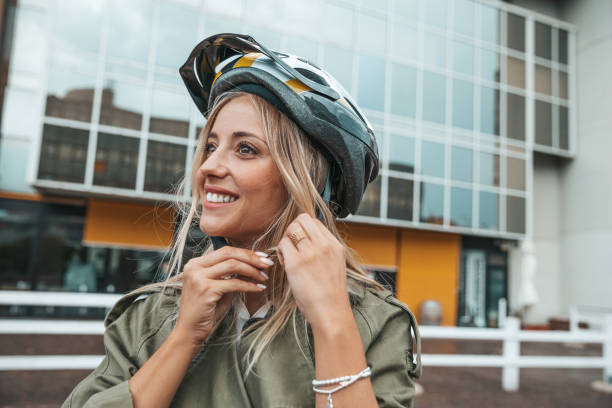Woman putting helmet on and ready to ride stock photo